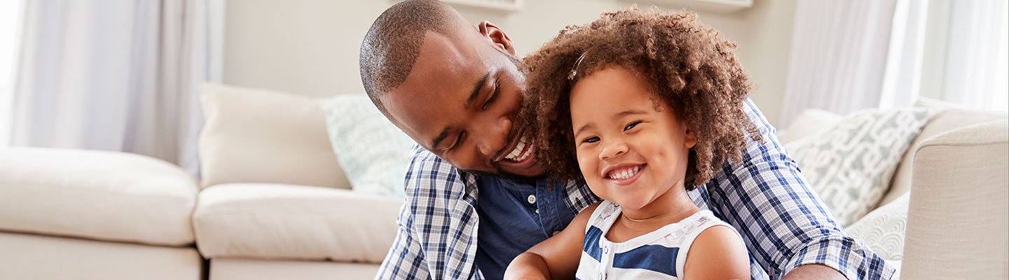 photo of father and daughter in living room sitting on floor, smiling and laughing